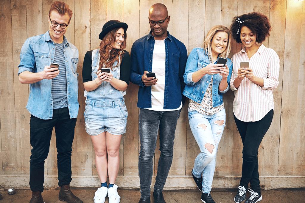 Grupa ludzi pokazuje sobie coś na telefonach.