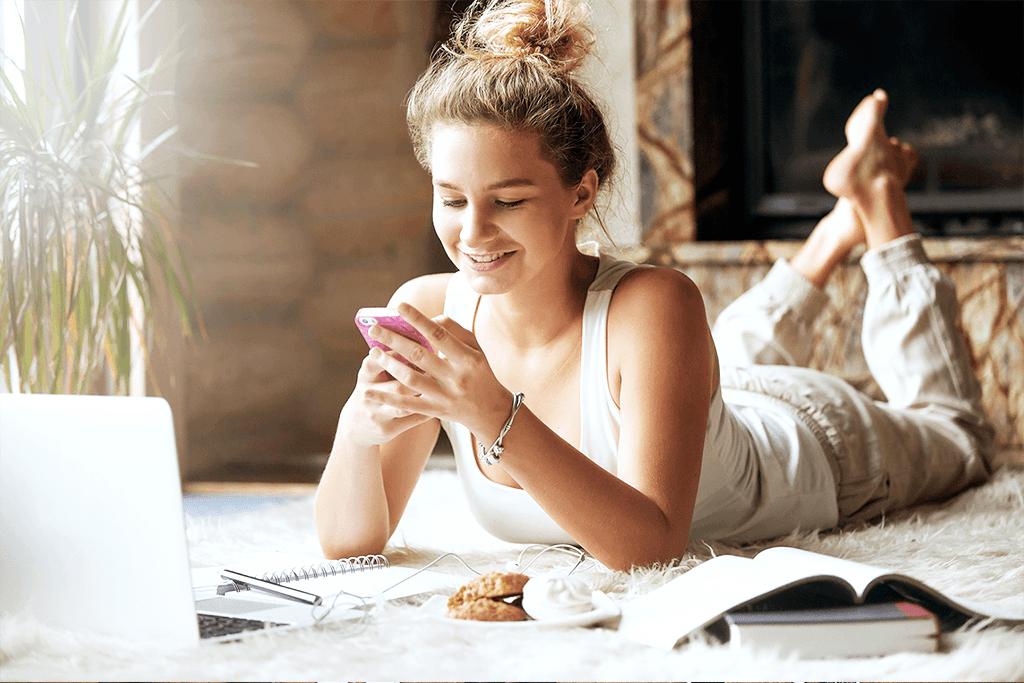 Kobieta pisząca sms podczas pracy na komputerze.