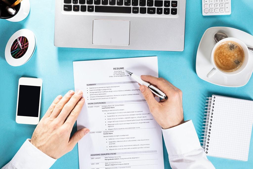 CV, kawa, laptop i telefon na biurku.