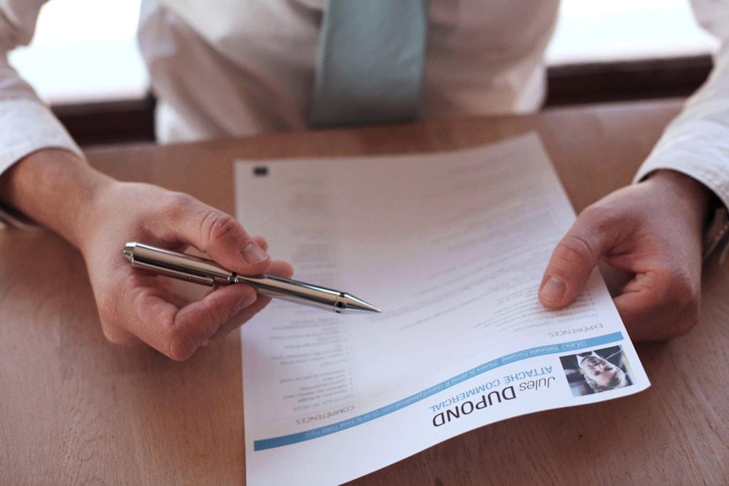 Pan trzymający CV i długopis.